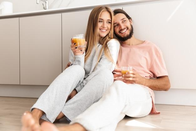 Lindo casal sorridente se abraçando enquanto está sentado no chão da cozinha, bebendo suco de laranja