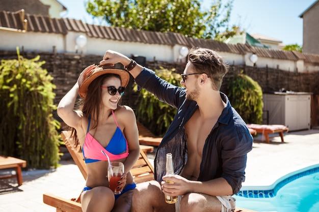 Lindo casal sorrindo, falando, bebendo cocktails, sentado perto da piscina