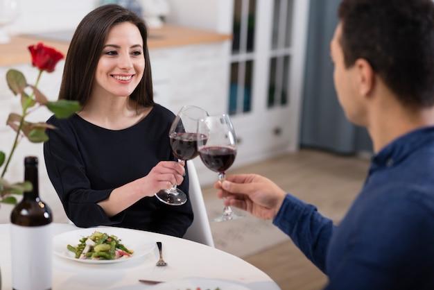 Lindo casal torcendo com taças de vinho