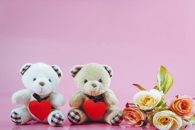 Lindo casal urso segurar o coração com fundo rosa
