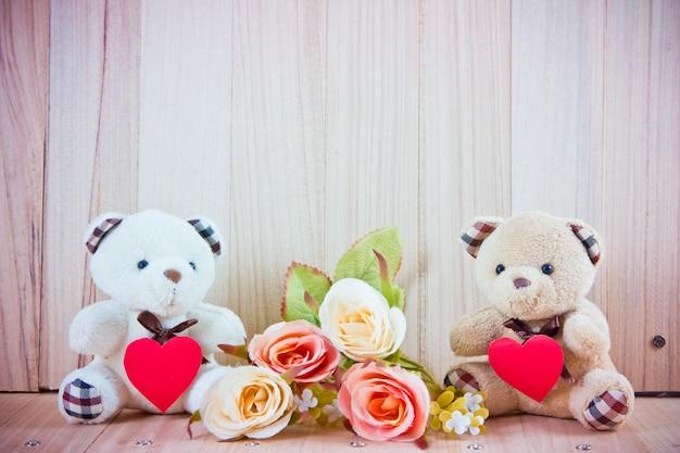 Lindo casal urso sente-se perto de rosas doces no chão