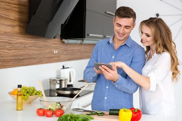 Lindo casal usando smartphone e cozinhando na cozinha de casa