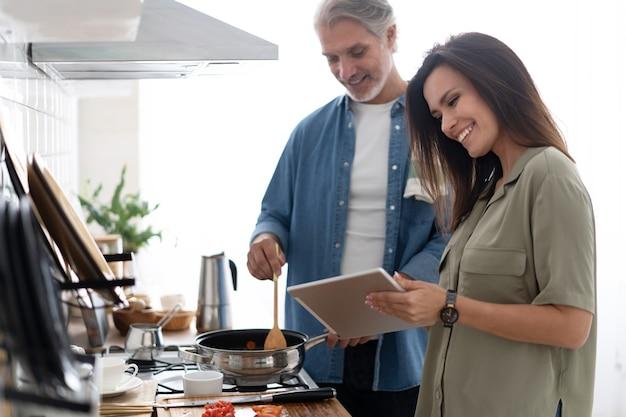 Lindo casal usando um tablet digital e sorrindo enquanto cozinha na cozinha de casa