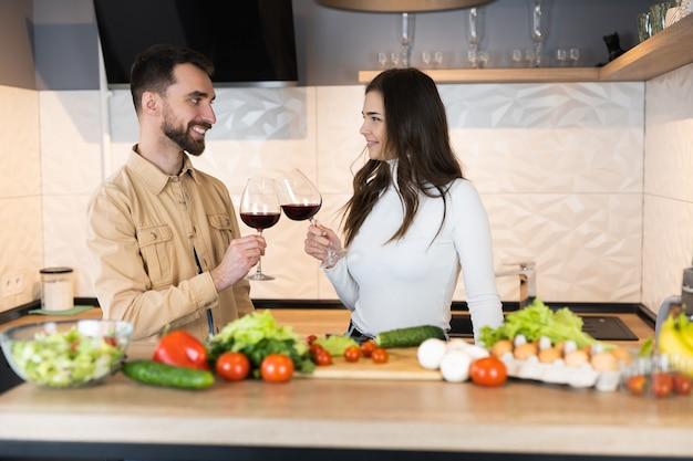 Lindo casal vegetariano está cozinhando e bebendo vinho tinto juntos em um encontro na cozinha doméstica.