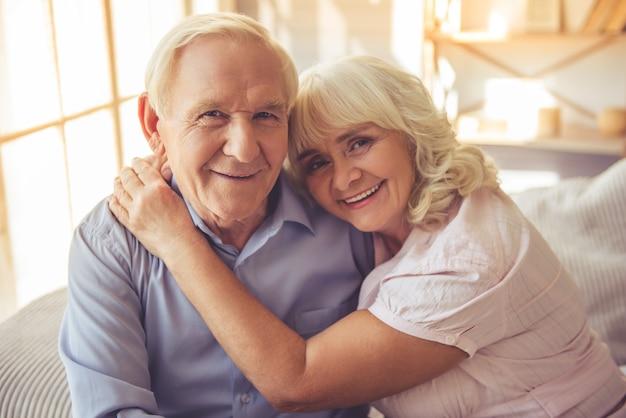 Lindo casal velho está abraçando, olhando para a câmera.