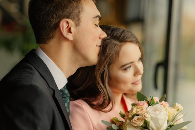 Lindo casamento, marido e mulher, noivos em pé no interior do sotão perto da janela. recém-casados casal apaixonado. noivo abraça a noiva pelos ombros.