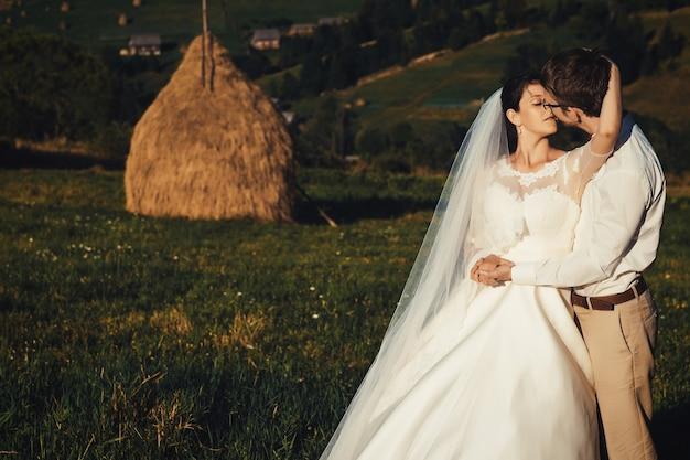 Lindo casamento nas montanhas, um jovem casal feliz perto do palheiro.