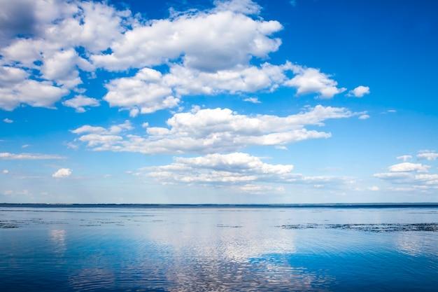 Lindo céu azul nublado e seu reflexo na água do reservatório de kaniv, ucrânia