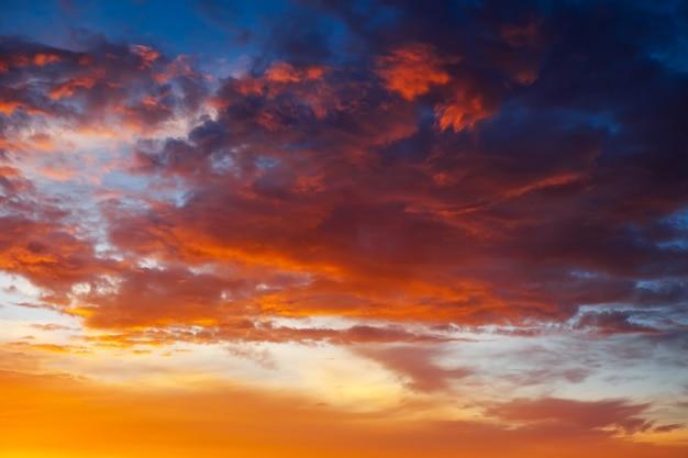 Lindo céu brilhante e colorido. foto tirada ao pôr do sol. fundo vermelho-laranja com belas tintas. nascer do sol raro. composição natural
