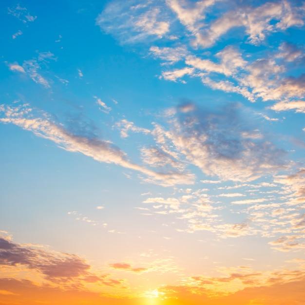 Lindo céu dramático ao nascer do sol. cores azuis e laranja do céu com nuvens brancas.