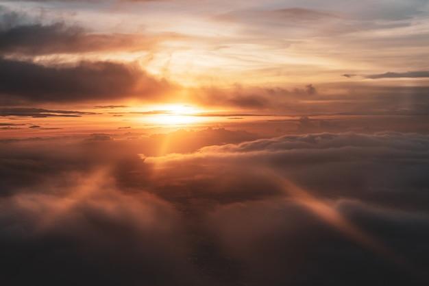 Lindo céu pôr do sol com raios de luz vista do avião