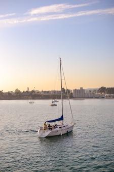 Lindo céu pôr do sol no mar ou lago e iate à vela de barco ao pôr do sol bela vista da natureza