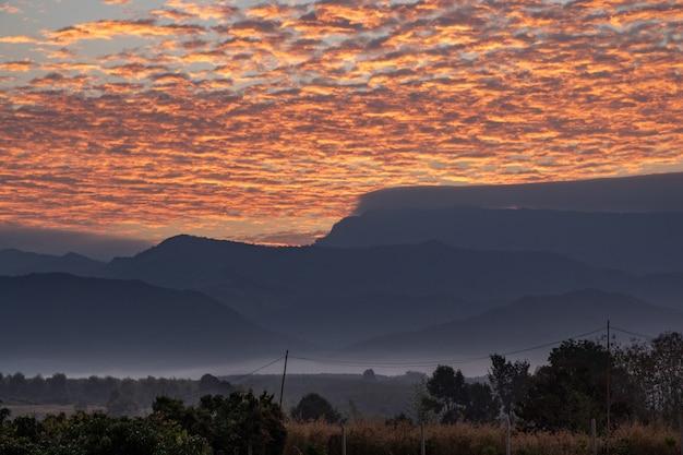 Lindo céu vermelho com nevoeiro no nascer do sol atrás de uma montanha.