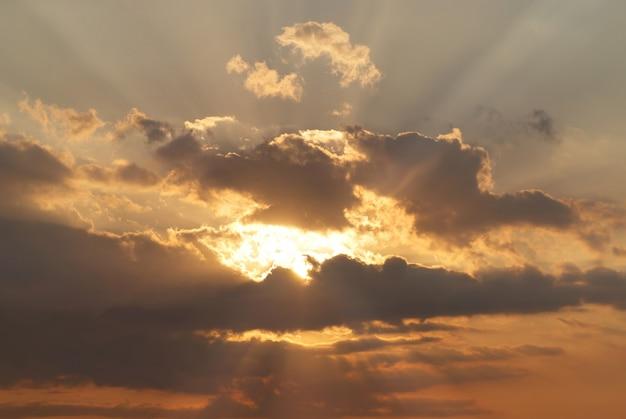 Lindo céu vermelho com raios de sol e nuvens