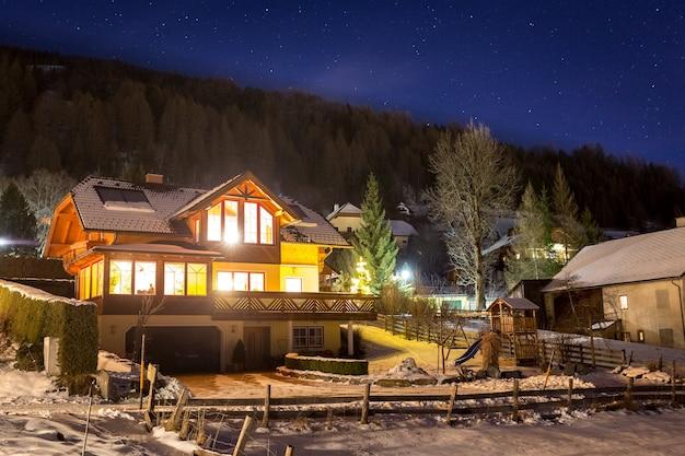 Lindo chalé de madeira nos altos alpes austríacos à noite estrelada