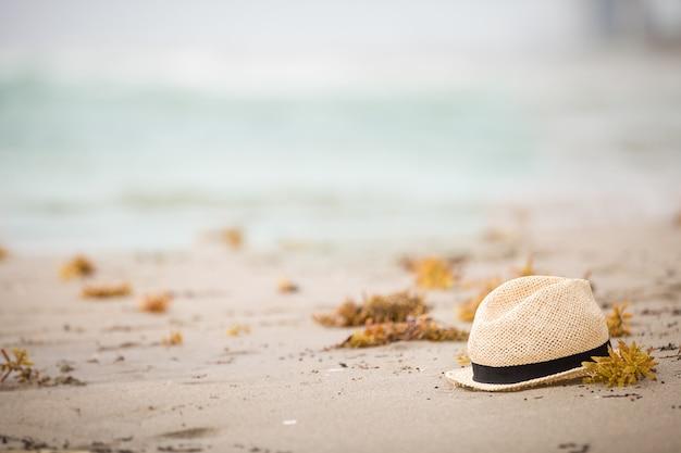Lindo chapéu de palha deitado na areia à beira-mar da praia