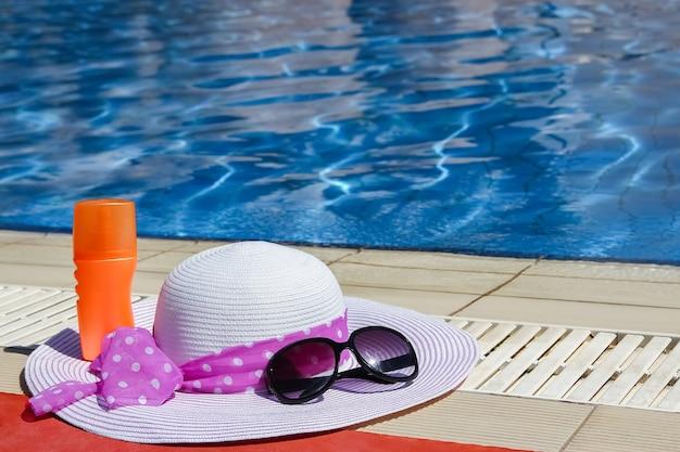 Lindo chapéu perto da piscina com fundo creme e óculos