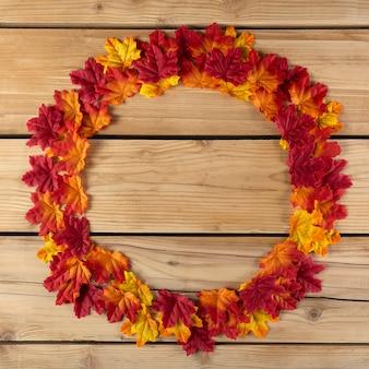 Lindo círculo de folhas de outono sobre a madeira