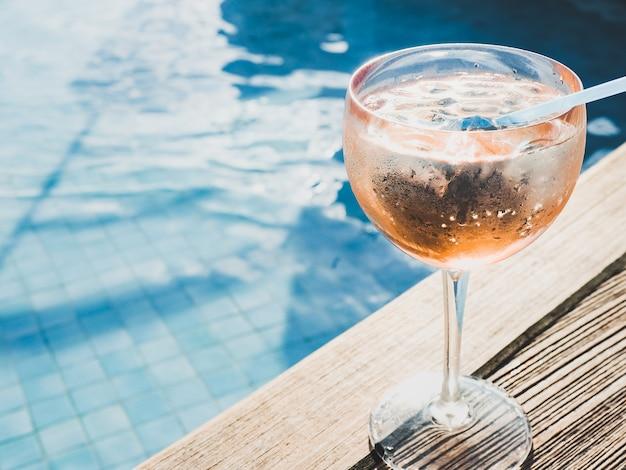 Lindo copo com um cocktail rosa e cubos de gelo