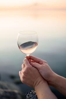 Lindo copo com vinho rosa nas mãos de uma jovem. copo de vinho ao nascer do sol. café da manhã romântico à beira-mar e sol