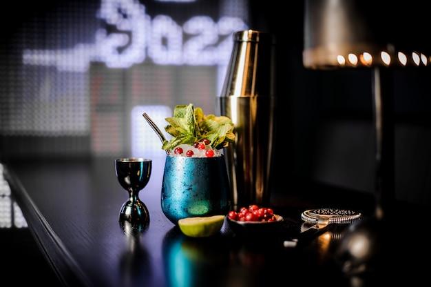 Lindo copo de cocktail azul com cocktail de verão decorado com frutas
