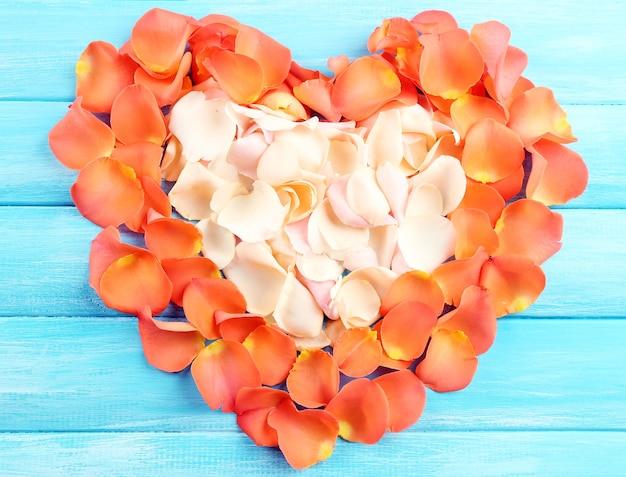 Lindo coração de pétalas de rosa em fundo de madeira