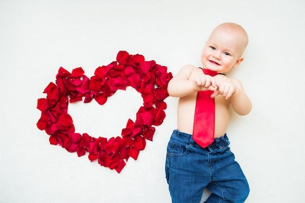Lindo coração de pétalas de rosa vermelhas e lindo garoto garoto em fundo branco. dia dos namorados, conceito de amor do dia das mães