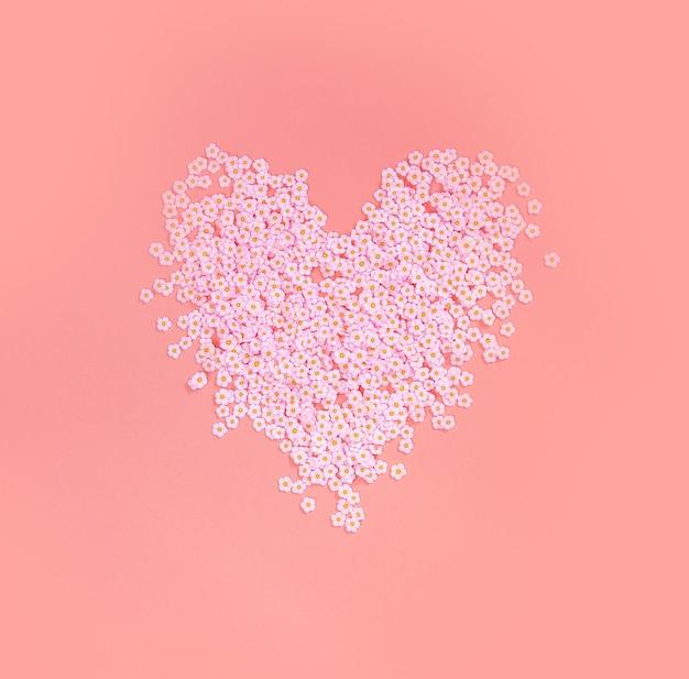 Lindo coração rosa feito de flores de margaridas rosa na vista superior de fundo colorido em tons pastéis, primavera, dia das mães, amor, plano de fundo do dia dos namorados