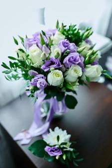 Lindo delicado buquê de noiva branco e roxo na mesa