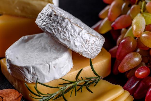 Lindo delicioso queijo camembert, parmesão, brie com uvas e figos em uma placa de madeira. petiscos para vinho no feriado
