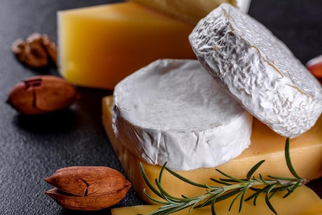 Lindo delicioso queijo camembert, parmesão, brie com uvas e figos em uma placa de madeira.
