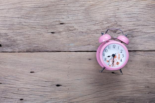 Lindo despertador rosa sobre fundo de prancha de madeira velha.