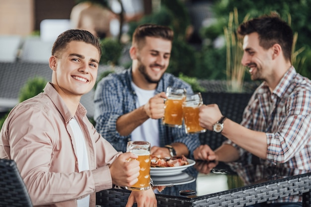 Lindo dia, três empresário sentar-se no terraço de verão no café e bebendo cerveja.