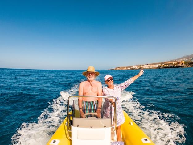 Lindo e fofo casal de idosos ou velhos no meio do mar, dirigindo e descobrindo novos lugares com um pequeno barco. mulher madura segurando um telefone e tirando uma selfie com o marido