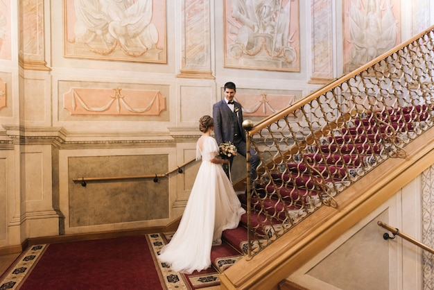 Lindo elegante casal de noivos apaixonados em um interior luxuoso nas escadas