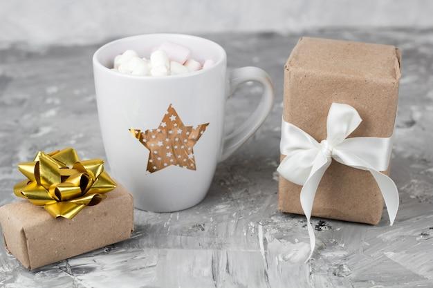 Lindo elegante copo com marshmallows e caixa de presente fundo cinza concreto
