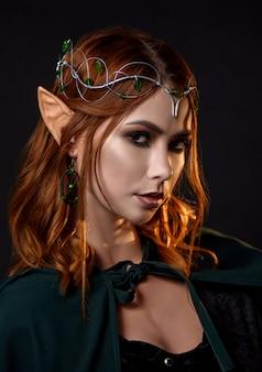 Lindo elfo na capa verde escura, olhando para a câmera.