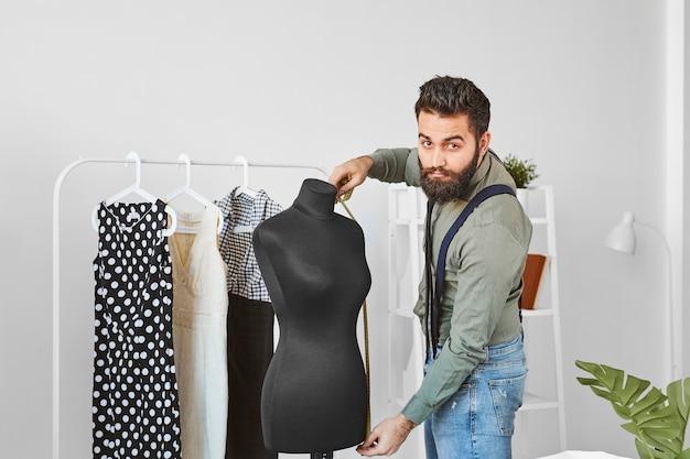 Lindo estilista masculino no ateliê com forma de vestido