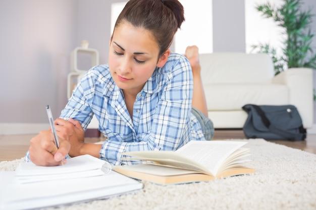 Lindo estudante morena fazendo o dever de casa deitado no chão