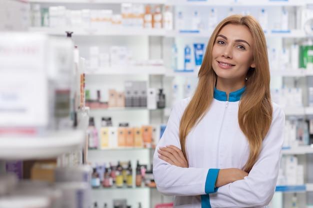 Lindo farmacêutico feminino em jaleco branco, posando orgulhosamente na farmácia, sorrindo para a câmera.