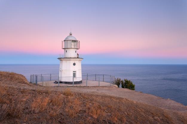 Lindo farol branco na costa do oceano ao pôr do sol