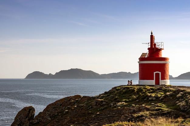 Lindo farol vermelho localizado em cabo do home e ilhas cies, cangas, galiza, espanha