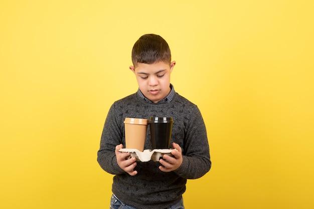 Lindo filho com síndrome de down, olhando para xícaras de café.