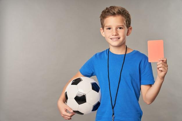 Lindo filho do sexo masculino com camisa azul, mostrando cartão de penalidade e sorrindo em pé contra um fundo cinza