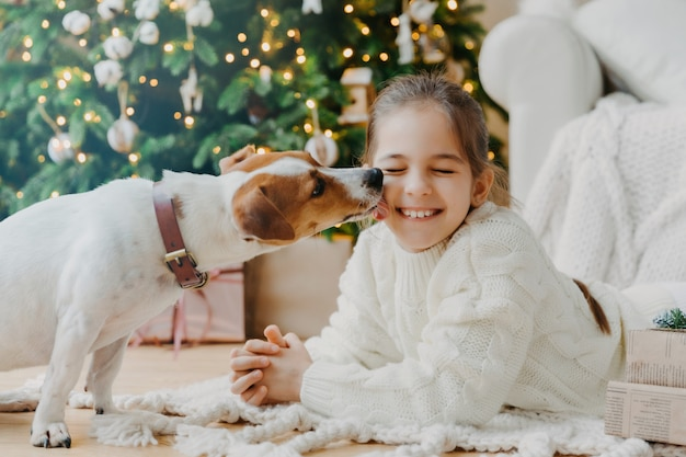 Lindo filhote de cachorro lambe a cara de chillds se divertir juntos posar no chão na acolhedora sala contra a árvore do abeto decorada, caixas de presentes.