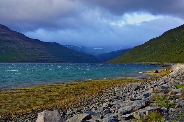 Lindo fiorde ao lado da estrada na islândia. céu nublado misterioso.