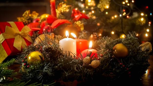 Lindo fundo de natal com velas acesas, luzes brilhantes e coroa do advento na sala de estar