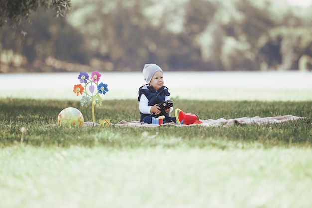 Lindo garotinho brincando com brinquedos sentado no gramado do parque