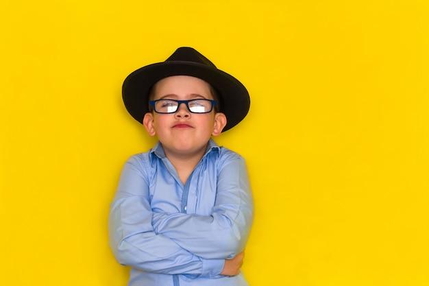 Lindo garotinho em um chapéu preto e camisa azul fica com os braços cruzados isolado no amarelo