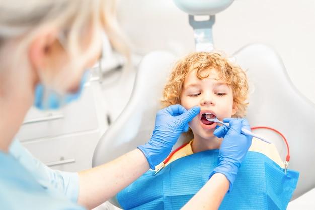 Lindo garotinho no consultório odontológico, tendo os dentes verificados por uma dentista.